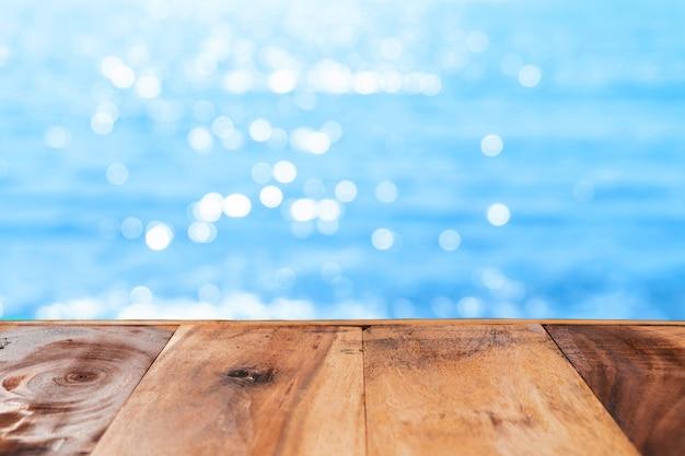 製品を表示するための美しいビーチの背景を持つ古い木製のテーブルの選択的な焦点。