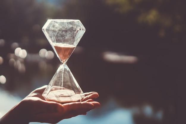 小さな砂時計のショーの時間が古い木材グランジテクスチャに流れています。