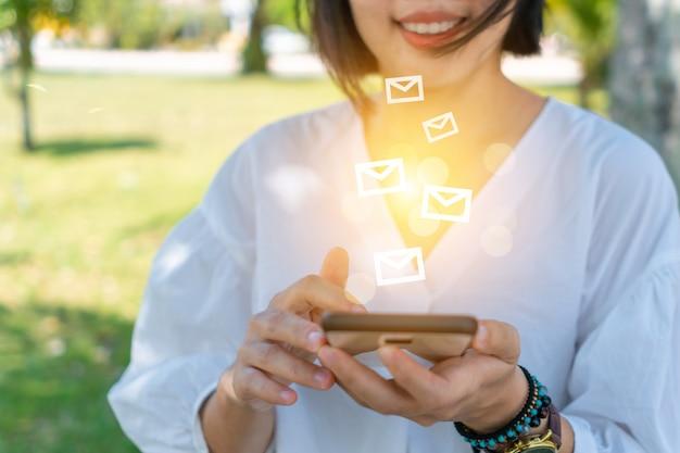 ビジネスのメールを送受信するためにスマートフォンを使用している女性の手。