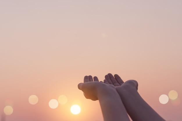 Женщина руки место вместе, как молиться перед природой зеленый фон.