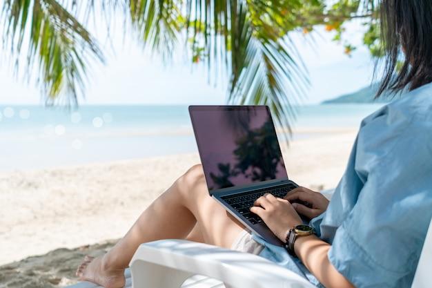 ノートパソコンとスマートフォンを使用してビーチの背景で休暇のキャディーで勉強する女性。