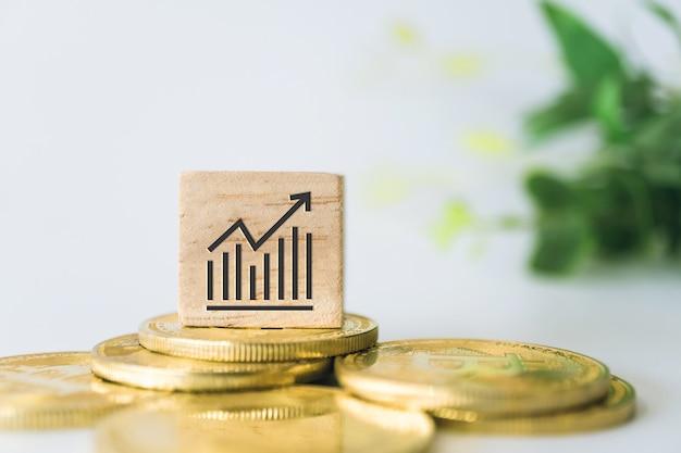 ゴールドコイン、電卓、ミニホームモデルなどのオブジェクトが木製の立方体に成長の指数記号を上昇するグラフは、白いきれいな壁を覆います。事業金融ローン物件。