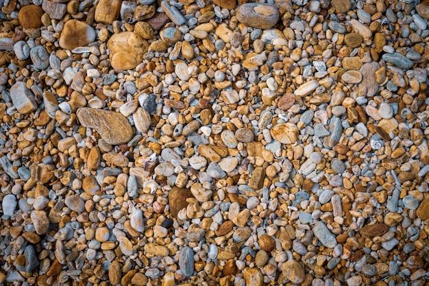 ビーチの茶色の色のトーンの背景テクスチャの小さな岩。