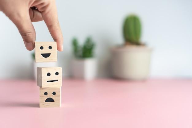 Улыбающееся лицо и значок корзины на деревянный куб. оптимистичный человек или люди чувствуют себя внутри и рейтинг обслуживания при совершении покупок, удовлетворение концепции.