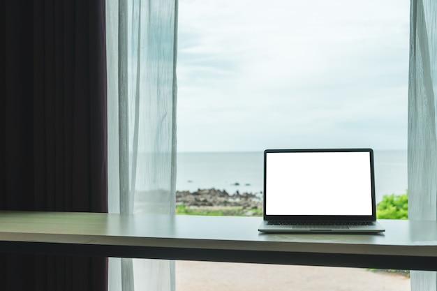 ノートパソコンとスマートフォンを使用してリゾートの部屋で休暇の日に勉強する女性。
