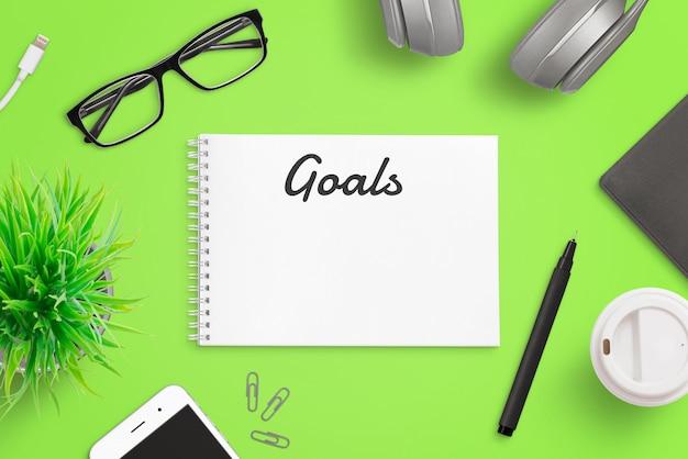 メモ帳ページのコンセプトに目標を書く。スマートフォン、メガネ、フォルダー、コーヒー、植物と緑のオフィスデスク。トップビューの構成。