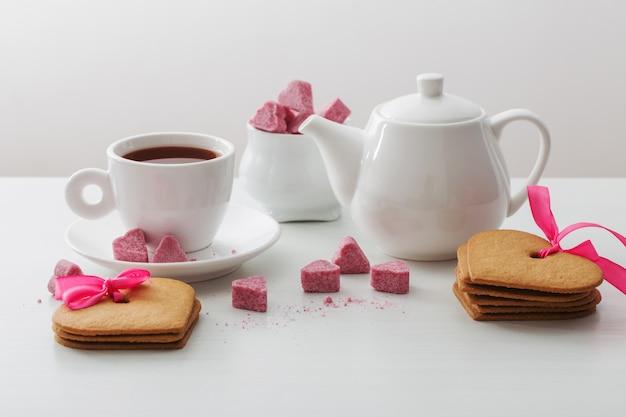 Гранулированный розовый сахар в форме сердца и чашка чая на белом фоне