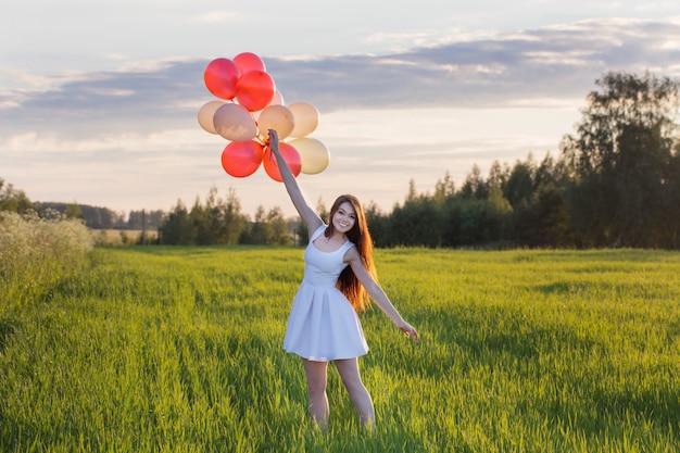 屋外の風船を持つ若い女性