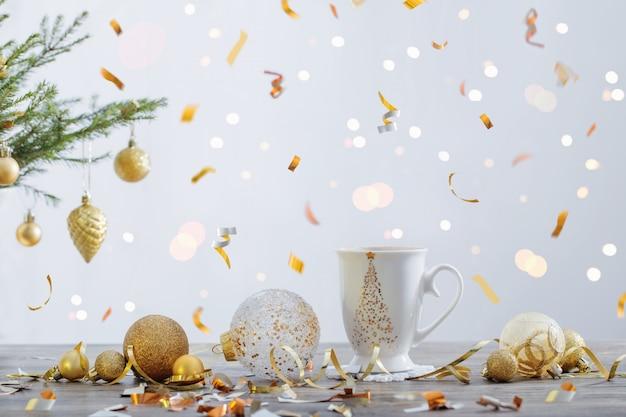 白いカップと白い背景の上のクリスマスの装飾