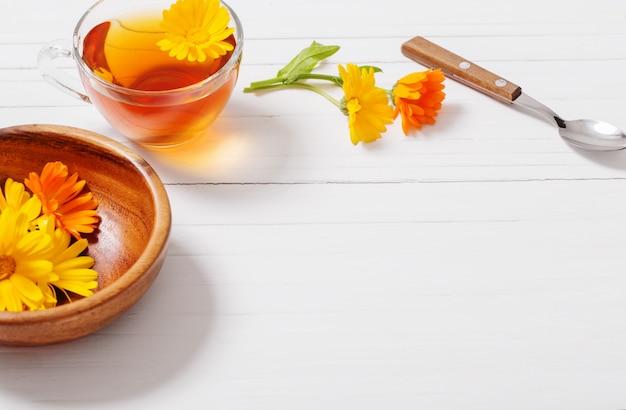 Травяной чай календулы (календулы) на белом деревянном столе