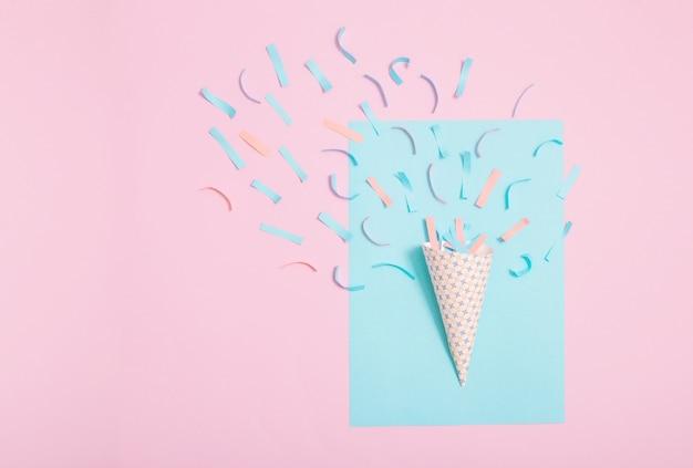 紙の背景に紙吹雪の誕生日帽子