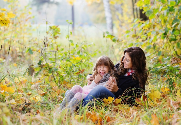 母と子は秋の公園で遊んでいます。