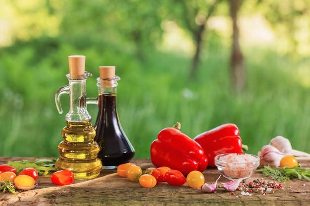 屋外の木製のテーブルに油と野菜