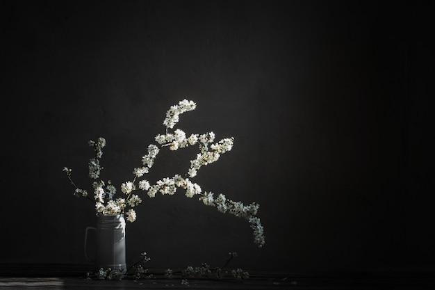 Цветы вишни в белом кувшине на старый деревянный стол