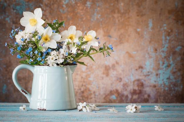 古い木製の塗られたテーブルの水差しの春の花