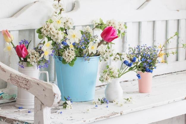 古い木製のベンチとヴィンテージの白いインテリアの春の花