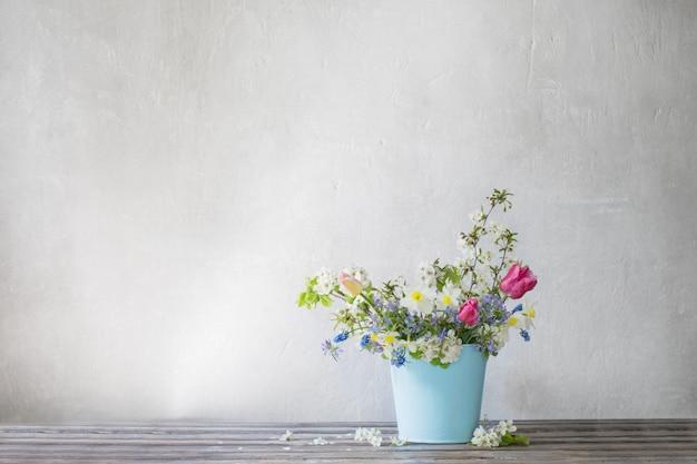 青いバケツの春の花
