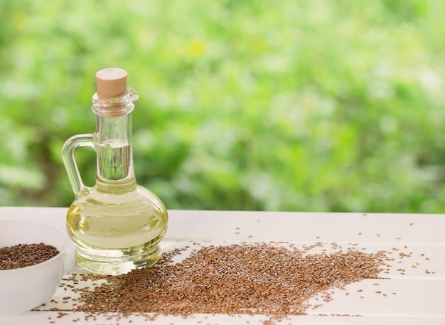 Семена льна и льняное масло в стеклянном кувшине на деревянном столе