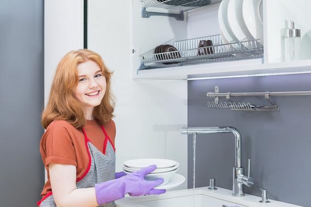 紫色のゴム手袋でティーンエイジャーの女の子が台所で皿を洗う