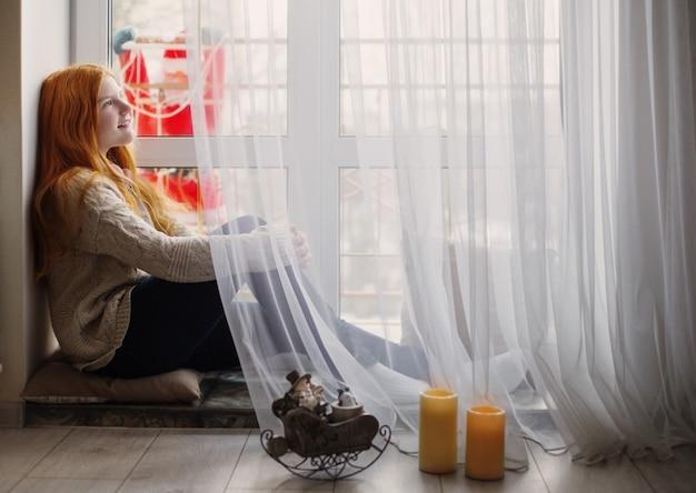 Улыбающаяся девушка у окна с дедом морозом