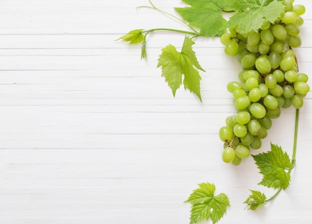Зеленый виноград на белом деревянном столе