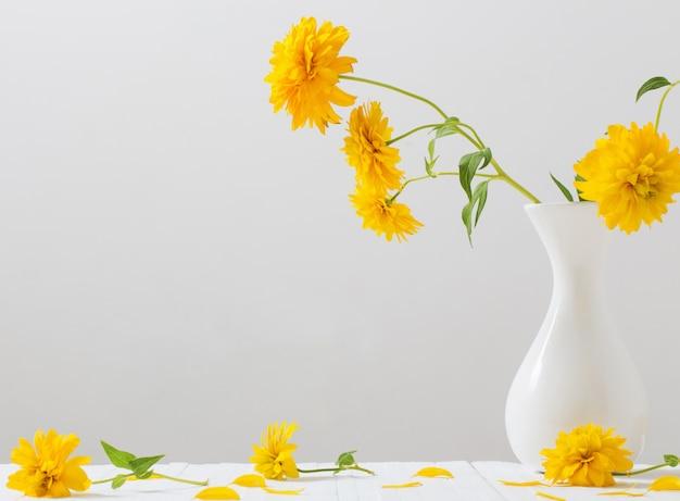Желтые цветы в вазе на белом фоне