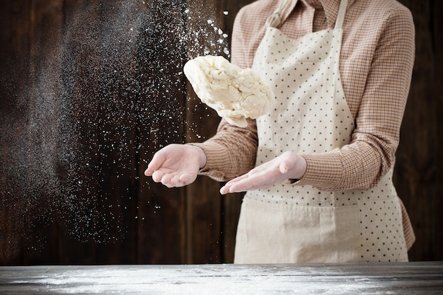 Руки готовят тесто на темном деревянном столе