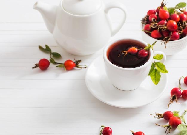 Чай с ягодами шиповника на деревянном столе