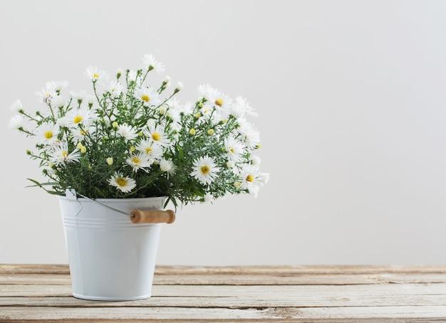Белые цветы на ведро на деревянный стол