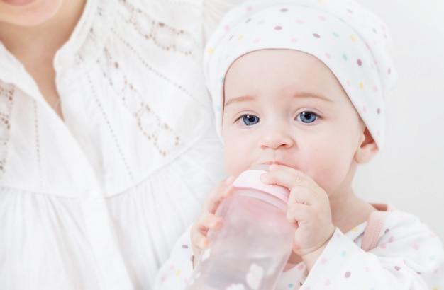 Мать кормит ребенка бутылочкой