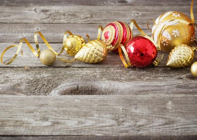 古い木製の背景にクリスマスの赤と金色のおもちゃ