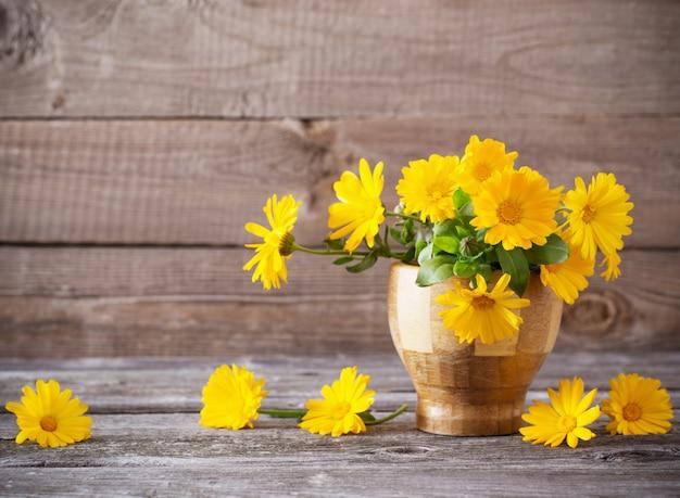 Цветки календулы на темном старом деревянном фоне