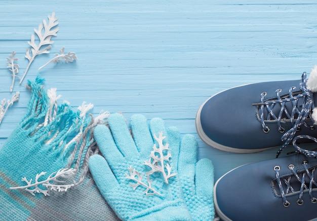 Синие зимние туфли и перчатки на синем фоне деревянных