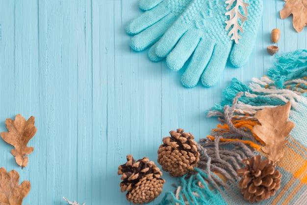 Синие перчатки и осенние листья на деревянном фоне