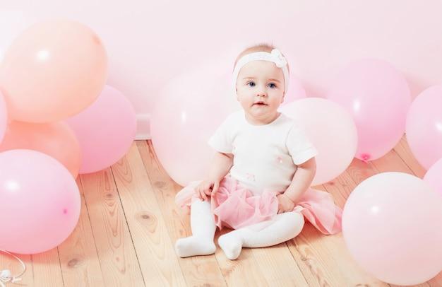 Красивая маленькая девочка с воздушными шарами в помещении