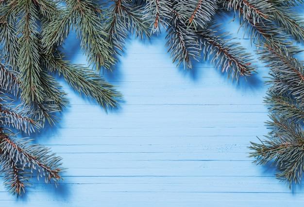 青い木製の背景にモミの枝
