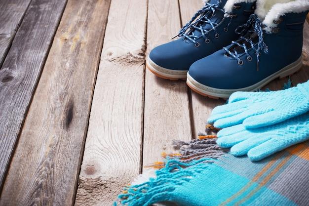 Зимняя обувь, перчатки, шарфы на старом дереве
