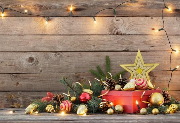 クリスマスのおもちゃと古い木製の背景に赤いボックス
