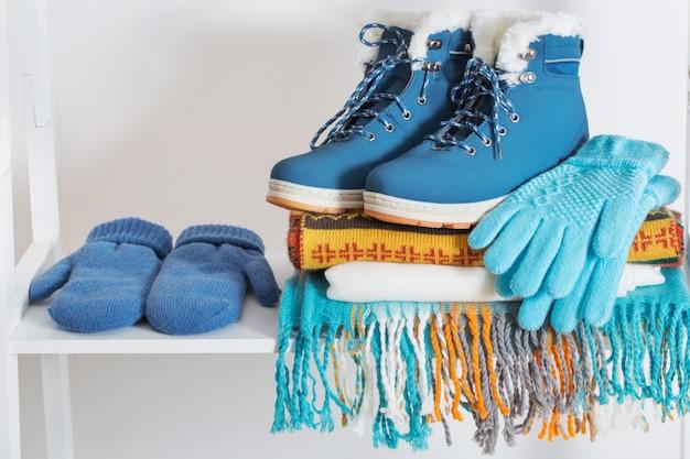 Зимняя обувь, перчатки и шарф на белой деревянной полке