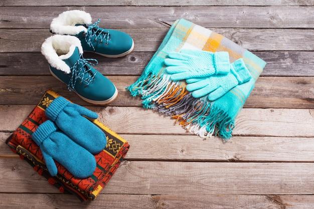 Зимняя обувь, перчатки, шарфы на старой деревянной стене