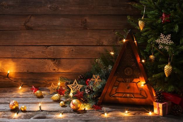 木製の壁にクリスマスツリーとヴィンテージ時計