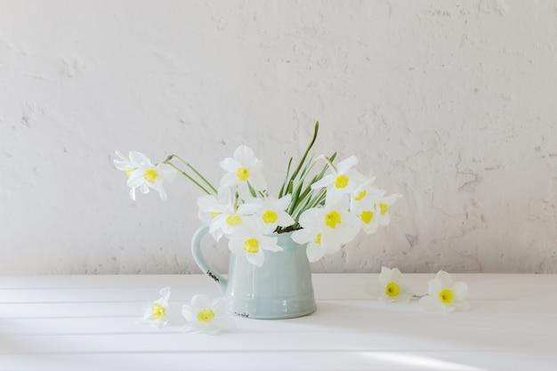 Нарциссы в кувшине на белом столе