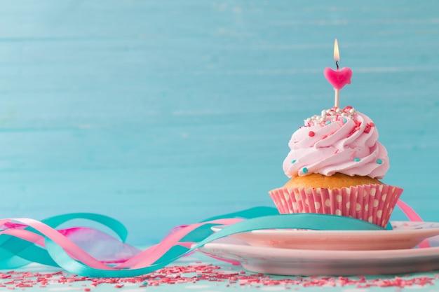 青い木製のテーブルにピンクのカップケーキ