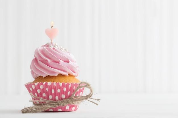 白い木製のテーブルにピンクのカップケーキ