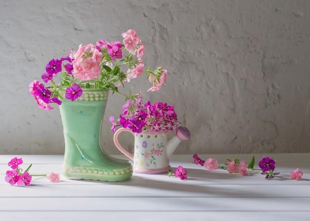 Летние цветы в керамическом ботинке на белом столе