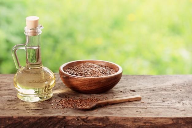 亜麻の種子と木製のテーブルのガラスの水差しの亜麻仁油