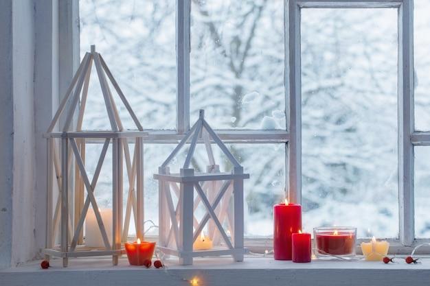 壁の冬の風景の窓辺に木製ランタン