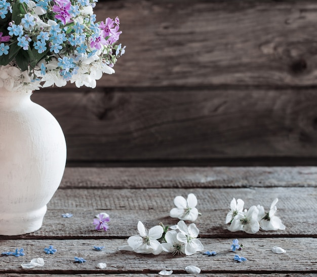 暗い背景の木の上に花瓶の春の花