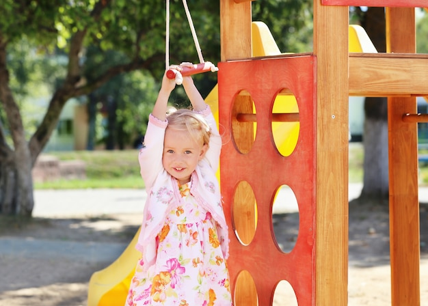 Счастливая маленькая девочка на детской площадке