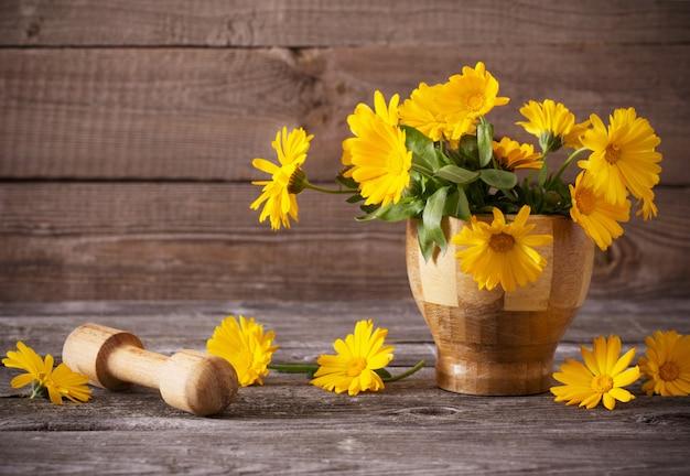 暗い古い木製の背景にキンセンカの花